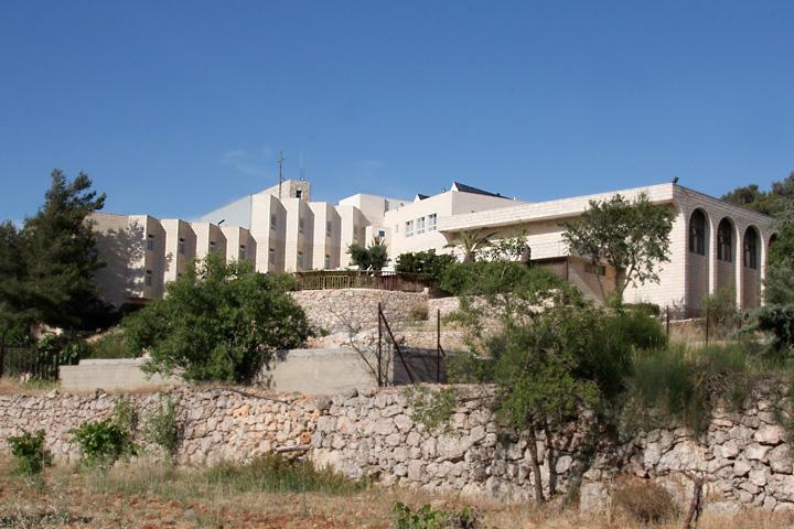 Inspektion - Schulgebäude über terrassiertem Gelände mit Bäumen und Trockenmauern