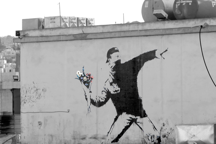 Begenungen in Talitha Kumi - Mauergraffiti von Banksy: Mann schmeißt Blumenstrauß statt Stein - Foto: Michael Rose (CC)