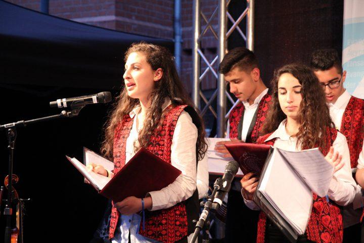 Zwei Schülerinnen und ein Schüler singen beim Auftritt des Chors