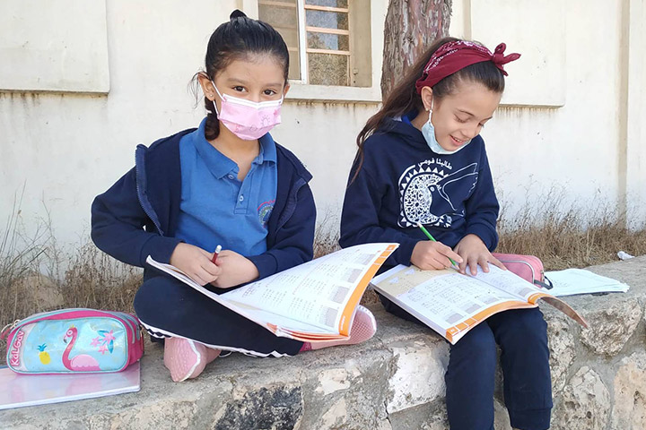 Spenden zu Advent - Schule Talitha Kumi bei Bethlehem, Foto: Zwei Schülerinnen sitzen auf kleiner Mauer und lernen